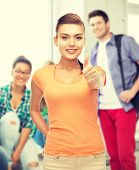 woman in blank t-shirt showing thumbs up at school