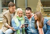 travel, vacation, technology and friendship concept - group of smiling friends with digital photocamera in the city