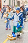 LIMA, PERU, MAY 25, 2014 - Street seller offers incenses during religious procession