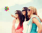 summer holidays, vacation and ecology concept - girls with windmill toy on the beach