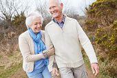Senior Couple Walking Through Winter Countryside