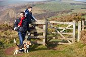Father And Son With Dog Walking Along Coastal Path