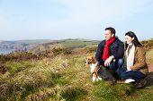 Couple With Dog Walking Along Coastal Path