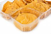 nachos chips with cheese sauce in plastic container on white background