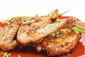 grilled meat : chicken quarters garnished with green sprouts and red peppers on red plate isolated o