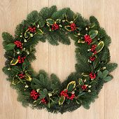 Winter and christmas floral wreath with holly, mistletoe and spruce fir over oak background.
