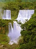 The grand Iguazu Falls on the Brazilian side. Multi-tiered cascades of water roar of lush jungle.