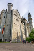 HOHENSCHWANGAU, GERMANY - 19 JUNE 2014: People outside of Neuschwanstein Castle in Hohenschwangau, Germany. Neuschwanstein castle is a nineteenth-century palace built for Ludwig II of Bavaria.