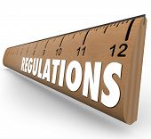 Regulations word on a wooden ruler measuring if you are within rules or guidelines for size, length or other standard