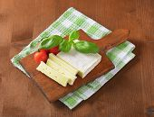mature surface ripened cheese with fresh tomatoes and herbs, served on the wooden cutting board
