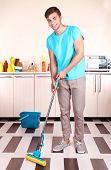 Young man cleaning floor in room