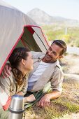 Outdoorsy couple smiling at each other inside their tent on a sunny day