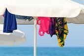 Sunshades And Clothes On A Sea Beach