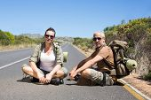 Hitch hiking couple sitting on the side of the road looking at camera on a sunny day