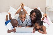 Happy family using laptop together on bed at home in the bedroom