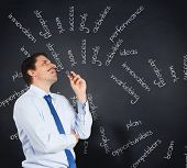 Thinking businessman biting glasses against blackboard with business buzzwords