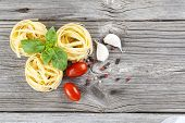 Italian Pasta Fettuccine Nest With Garlic, Tomatoes And Fresh Basil Leaves, On Wooden Background
