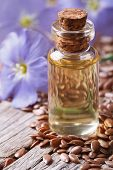 stock photo of flax seed oil  - flax oil in a glass bottle macro on a background of flowers and seeds vertical