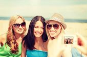 summer holidays and vacation concept - smiling girls taking photo with digital camera in cafe on the