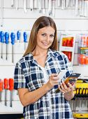 Portrait of female customer scanning product's barcode through mobilephone in hardware store