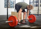 Full length of fit young man picking barbell in box
