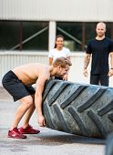 pic of strongman  - Side view of young athlete lifting tire outdoors - JPG