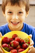 little cute boy eating strawberry close up