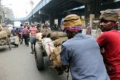 KOLKATA - FEB 15: Hard working Indians pushing heavy load through streets on February 15, 2014 in Ko