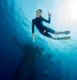 image of bottomless  - Free diver on depth with ship wreck on the background - JPG