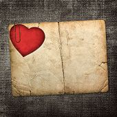 Old Paperboard Card With Red Paper Heart On A Dark Fabric Backgr