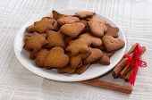 stock photo of cinnamon  - pepper cinnamon cookies on a white plate and cinnamon tied a red ribbon - JPG