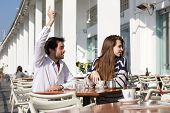 Young Man Sitting At Outdoor Cafe With Raised Arm Asking For Waiter