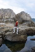 young man in scarf with coat sitting on a rock at the sea