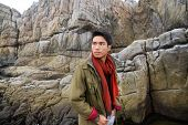 portrait of young man on a rock at beach background