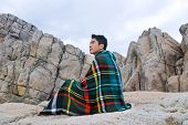 young man warmed up in plaid pattern scarf sitting on a rock at beach