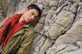 portrait of young man a rocky beach watching the ocean
