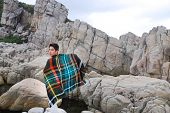 Young man with plaid pattern scarf on a rocky beach watching the ocean