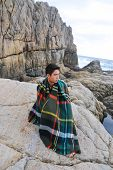 young man in plaid pattern scarf sitting on a rock at the sea
