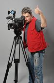 Cameraman in red vest, shows gesture