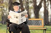 Mature college professor reading the news in park seated on a bench
