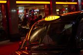 Low key detail of London black cab sign turned on at night, with red shop lights in the background.