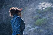 Young Nepalese woman standing in the water spray from a waterfall