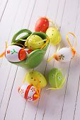foto of paint pot  - Colorful easter eggs in pot on white painted wooden planks - JPG