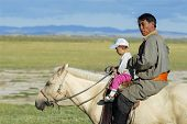 Mongolian man rides on horseback with a kid, Harhorin, Mongolia.