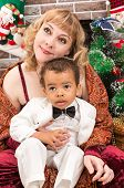 picture of new years baby  - Happy mother and black baby boy cuddling by fireplace - JPG