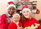 Happy Family: Black Father, Mom And Baby Boy Dressed Costume Santa Claus By Fireplace. Christmas And