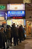 LONDON, UK - JANUARY 02: People lined up for discounted theatre tickets at night in Leicester Square. January 02, 2015 in London.