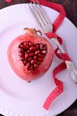 Pomegranate seeds in the form of heart on a wooden background