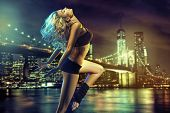 Active blonde beauty on evening city sky background