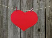 Large red heart hanging on clothesline by wood fence